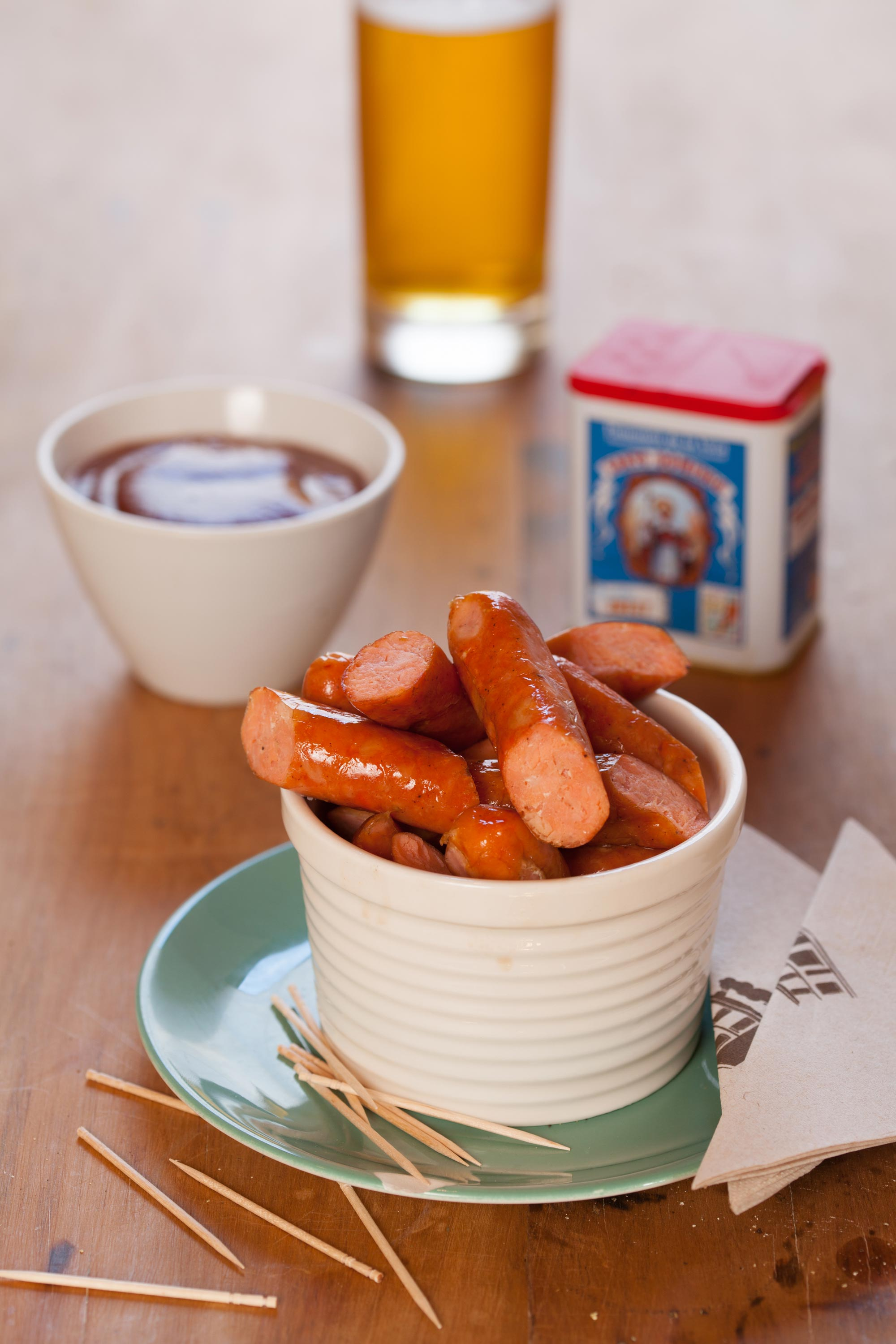 Salmon sausage cit into 1/3rds in a bowl with a dip